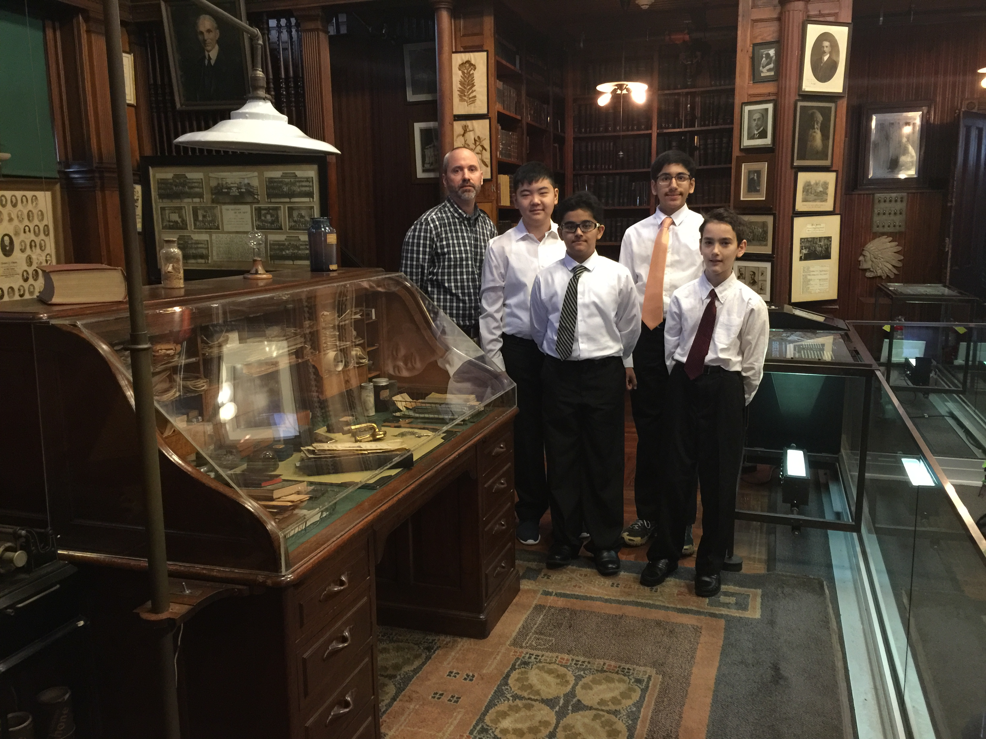 The winners and their teacher mentor pose near the historic desk of famed inventor Thomas Edison on display at TENHP.