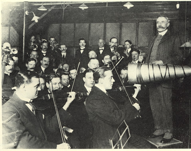 A private off-site recording session-with musicians crowded in close to recording horn