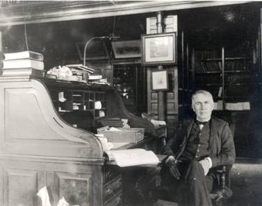 Edison at his roll-top desk, ready for work in his library-office.