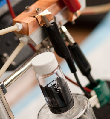 A sample of 'Cambridge crude' — a black, gooey substance that can power a highly efficient new type of battery. A prototype of the semi-solid flow battery is seen behind the flask. | Photo: Dominick Reuter