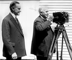 President Calvin Coolidge looks on as Edison works his motion picture apparatus