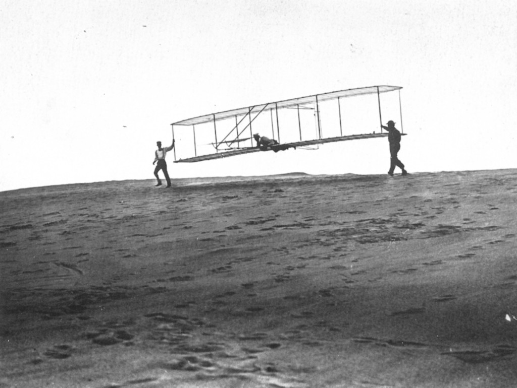 Orville being launched for an early flight in 1902. Brother Wilber and a friend are at each wingtip.