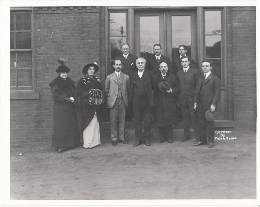 December 18, 1913: Visit of Orville Wright to Edison's West Orange Labs.  Front row l. to r. Mina Edison, daughter Madeleine, Orville Wright (light-colored suit), Thomas Edison, [unknown], John Sloane –husband of Madeleine.