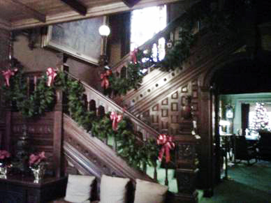 """This view greets all visitors to Glenmont at Christmas- the incredible main staircase to the second floor; and to the right the dining room and Christmas tree. It's a showstopper for all who like to """"Ohhhh"""" and """"Ahhhh""""."""