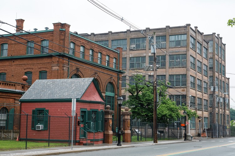 Old battery building shown at right of main gate and invention factory