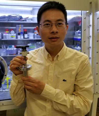 Postdoctoral scholar Wei Chen holds a prototype of Stanford's water-based battery.