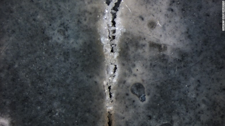Dark slab of concrete with crack that you can see crystalizing to heal itself