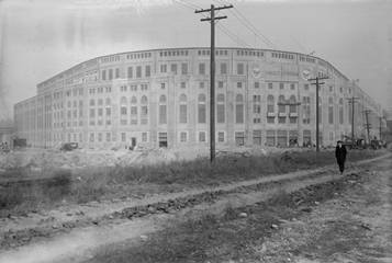 Yankee Stadium circa 1923 with man walking down dirt road next to itDescription automatically generated